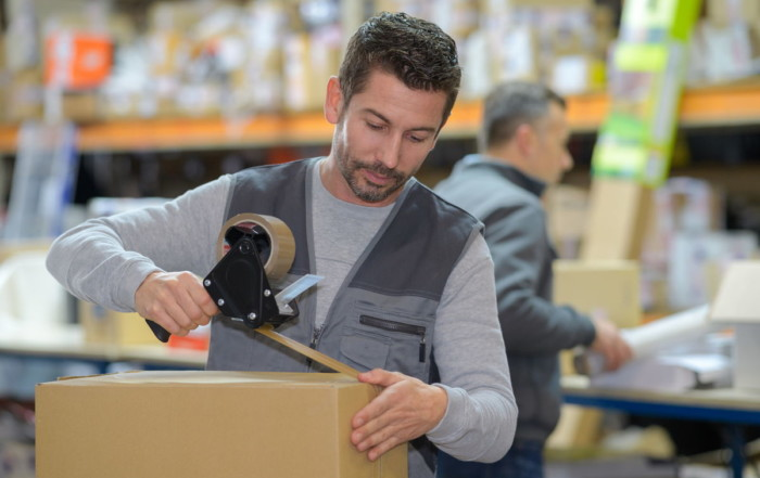 Blog man holding packing machine and sealing cardboard PYHYFB5 700x441
